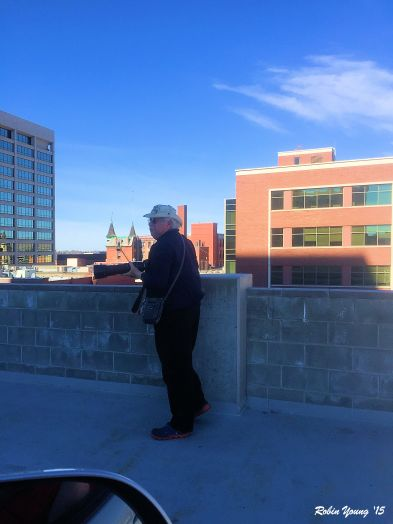 Robin took this of me looking at the peregrine on the ledge in fron of the box. See him? Top floor at the breezeway in the white building.